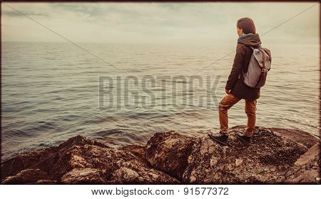 Girl standing on coast. Vintage effect