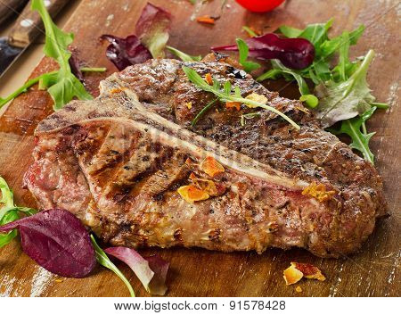 Steak With Fresh Herbs On A Rustic Wooden Board
