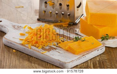 Grated Cheddar Cheese On  Wooden Board.