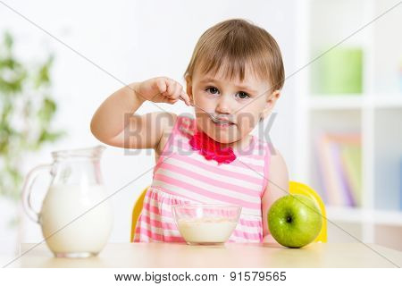 child eating food itself with spoon