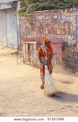 Woman Of Fourt Class In Brightly Colored Clothing Cleans The Street
