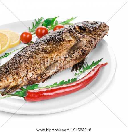 Grilled carp with vegetables on plate.