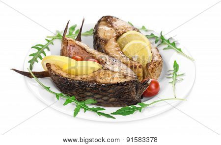 Grilled carp steaks with lemon and tomatoes.