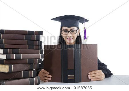 Student With Graduation Gown Studying