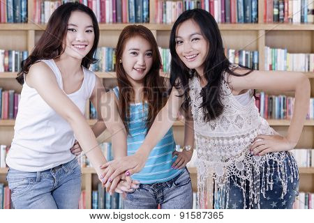 Three Casual Student Joining Hands
