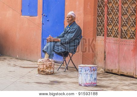 MARRAKESH, MOROCCO, APRIL 3, 2015: Elderly local man rest on chair in front of house