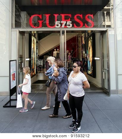 NEW YORK CITY - FRIDAY, MAY 8, 2015:  Pedestrians walk past a Guess Clothing retail store in Manhattan. Guess is an American upscale clothing brand and retailer.
