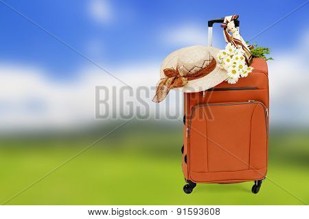 Travel bag with a straw hat and a bouquet of daisies on abstract nature background