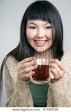 A beautiful young Chinese Asian Oriental woman  drinking tea