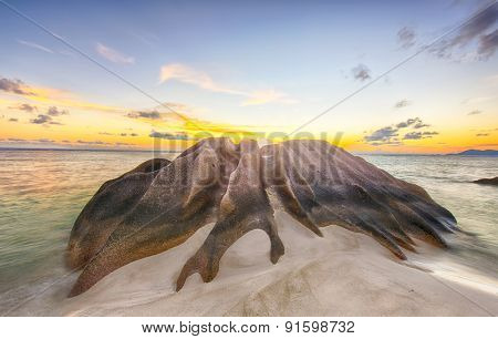 Beautifully shaped granite boulder is washed by sea at Anse Source d'Argent beach, La Digue island, Seychelles.Sunset time