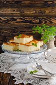 image of sponge-cake  - Cut the slices of sponge cake with pineapple rings on a wooden table - JPG