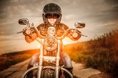 picture of biker  - Biker girl in a leather jacket and helmet on a motorcycle - JPG