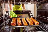 picture of oven  - Housewife preparing cakes in the oven at home - JPG
