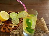 stock photo of mojito  - Glass of ice cold mojito on wooden table - JPG