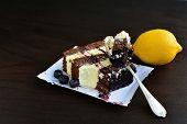 stock photo of sponge-cake  - Cocoa sponge cake with lemon cream and blueberry sauce over dark background - JPG
