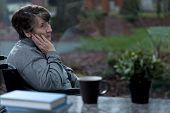 stock photo of depressed  - Depressed women sitting in a wheelchair at home - JPG