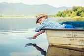 stock photo of old boat  - Little boy launch paper ship lying in old boat - JPG