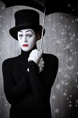 picture of loneliness  - Portrait of a male mime artist standing under umbrella expressing sadness and loneliness - JPG