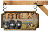 foto of milk  - Wooden and metallic sign with text Milk steel cans for the transport of milk and cows grazing - JPG