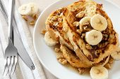 picture of french toast  - Plate of delicious French toast with bananas walnuts and dripping maple syrup overhead view - JPG