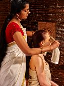 stock photo of ayurveda  - Young woman having head ayurveda spa treatment in India salon - JPG