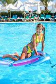 foto of mattress  - Little girl swimming on inflatable beach mattress - JPG