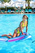 image of mattress  - Little girl swimming on inflatable beach mattress - JPG