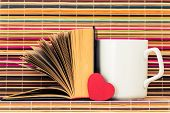 foto of memory stick  - The white cup the opened book and red heart before them on a color background from bamboo sticks - JPG