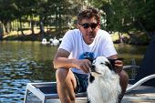 stock photo of dock  - Dog enjoying attention from has owner on the cottage dock at the lakehouse - JPG