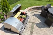 pic of grilled sausage  - Grilling healthy food with corn kebabs meat and sausages on an outdoor gas barbecue on a luxury brick paved patio and summer kitchen in a neatly manicured back yard - JPG