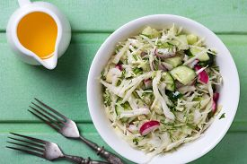 image of grated radish  - Salad from cabbage herbs cucumber onion and radish in bowl on green wooden background - JPG