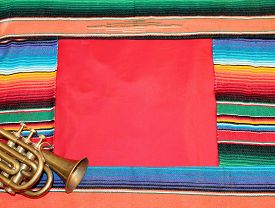 stock photo of mexican fiesta  - Traditional Mexican fiesta poncho rug in bright colors with sombrero background with copy space - JPG