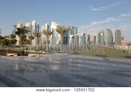 DOHA, QATAR - FEBRUARY 17 2016: The high rise business district of the Qatari Capital, seen from behind a water feature in Hotel Park.