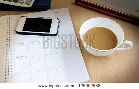 White Cup Of Remain Coffee In Dim Light Office Room With Background Of Cellphone, Organizer Book Wit