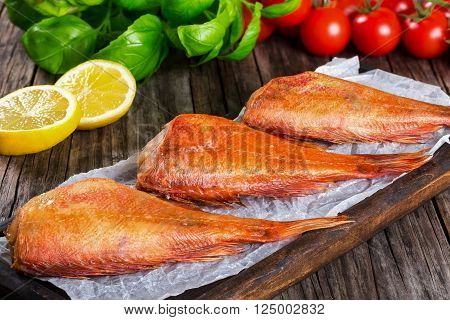Red Sea Bass on a parchment paper on an old wooden table with basil leaves lemon slices and cherry tomatoes on the background horizontal close-up top view