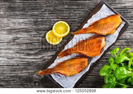 Red Sea Bass on a parchment paper on an old wooden table with basil leaves lemon slices on the background top view
