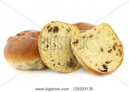 freshly baked traditional dutch raisin buns and two halves on a white background