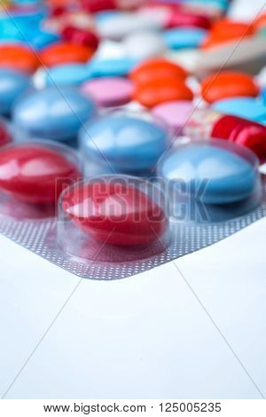 Pack op red and blue pills many coloured pills of different size at background. Close up. Concept of medicine.