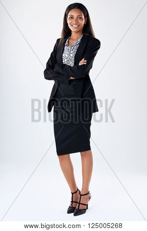 Full length business woman portrait wearing a black suit, smiling with arms crossed