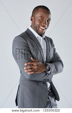 Confident black businessman in suit smiling in studio