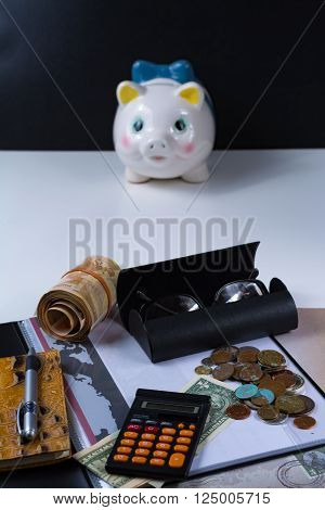 Piggy bank and business assesories glasses calculator on white background