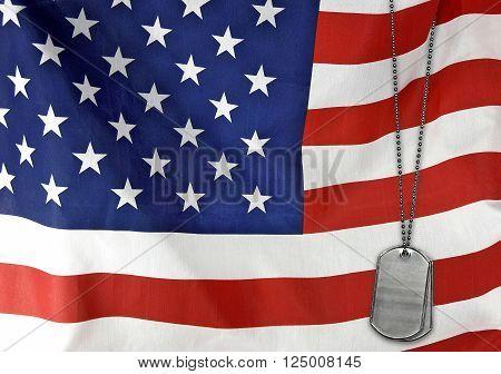 Military dog tags on an American flag.
