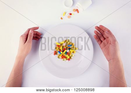 Different diet pills in white plate and female hands, isolated on white
