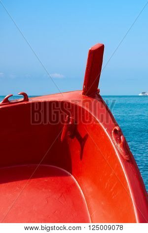 Detail of a wooden red prow of a rowing boat with sea in background. Liguria, Italy
