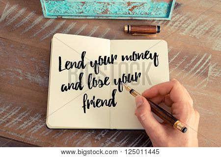 Retro effect and toned image of a woman hand writing on a notebook. Handwritten quote Lend your money and lose your friend as inspirational concept image