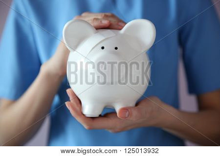 Woman holding in hands white piggy bank with patch
