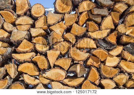 Wooden pattern. Stack of firewood at blue sky background
