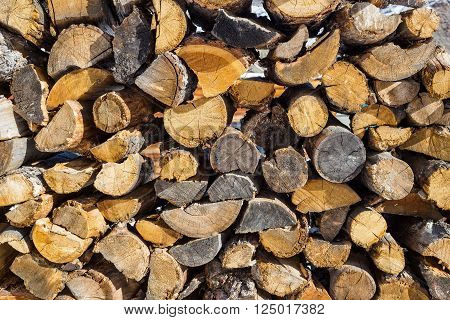 Wooden pattern. Stack of firewood at winter.