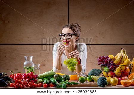 Young and cute woman eating grapes at the table full of fruits and vegetables in the wooden interior. Healthy food concept. Beauty and wellbeing