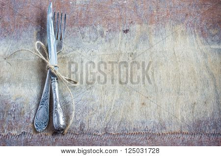 vintage silverware with burlap rope on wooden table